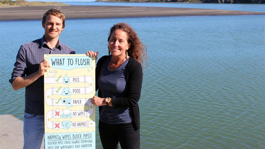 Raglan graphic designer Leighton Davies and Raglan Ward Councillor Lisa Thomson show an example of a poster produced for Waikato District Council's wastewater system public education campaign.